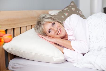 white linen: Sonriente mujer mayor intenta conciliar el sue�o en la cama con s�banas blancas Foto de archivo