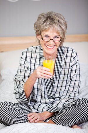 rejuvenated: Portrait of happy senior woman holding orange juice glass in bed