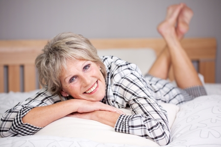 rejuvenated: Happy senior female lying in bed inside the living room