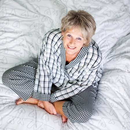 Top view shot of senior female sitting in bed at the living room photo