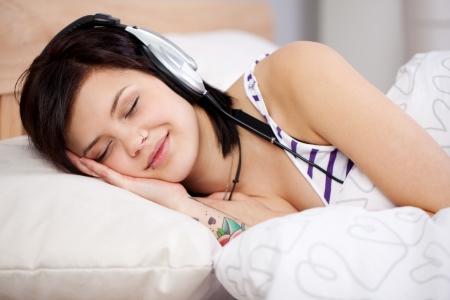 personas escuchando: Sonriente mujer acostada en la cama y sentir la música a través de auriculares