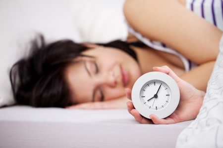 oversleep: Young woman holding clock while sleeping in bed