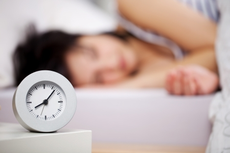 snooze: Close up image of alarm clock over the blurred sleeping woman