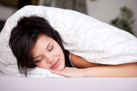 comforter: Smiling beautiful female fall asleep in bed with white linen