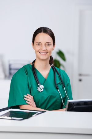trained nurse: Portrait of smiling nurse at counter in hospital