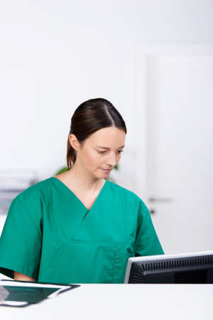 mid adult female: Mid adult female surgeon looking at computer at desk Stock Photo
