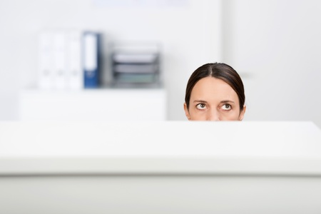 Mid adult businesswoman looking up in office cubicle photo