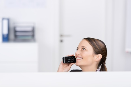 Happy businesswoman using cordless phone while looking up in office photo