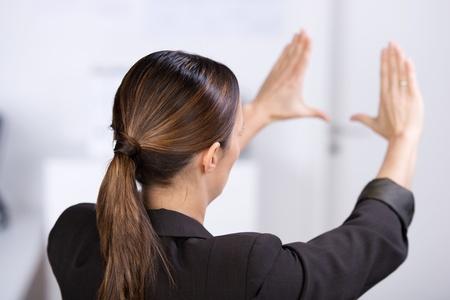 percepción: Vista posterior de mediados de negocios para adultos haciendo marco a mano en la oficina Foto de archivo