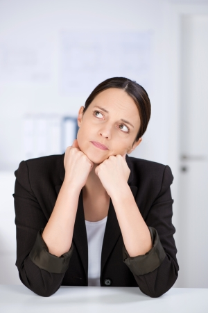 Mid adult businesswoman looking away while leaning on desk photo