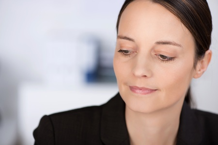 withdrawn: Closeup of confident businesswoman looking down in office