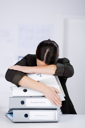 unsatisfied: Tired businesswoman leaning on stack of binders at desk in office
