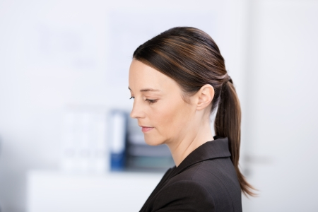 downcast: Closeup of beautiful businesswoman looking down in office Stock Photo