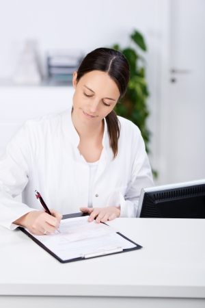 Mid adult receptionist signing prescription on clipboard at hospital reception photo