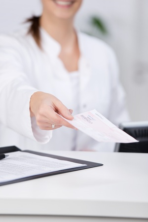 Midsection of receptionist giving check at hospital counter photo