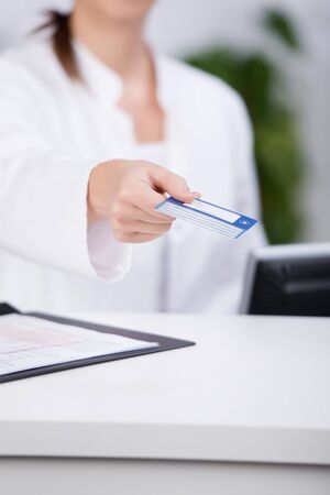 doctor holding money: Midsection of receptionist giving credit card at counter in hospital Stock Photo