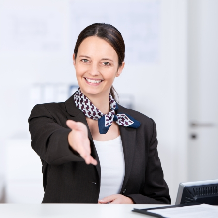 Portrait of happy receptionist offering handshake at counter photo