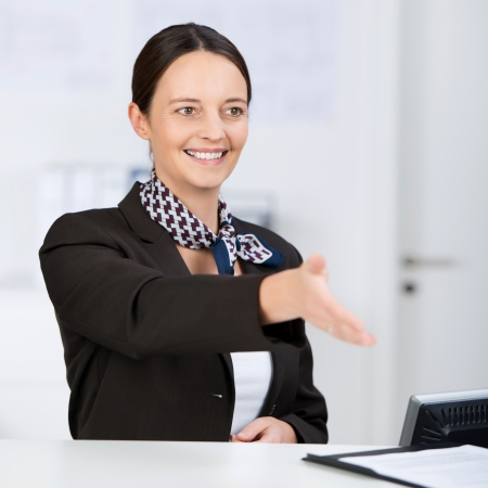 Portrait of smiling receptionist offering handshake at counter photo
