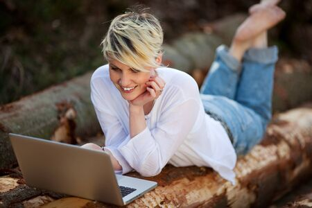 weekend break: Happy young woman with laptop lying on logs Stock Photo