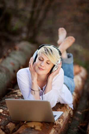 Young woman enjoying music on log with headphones and laptop photo