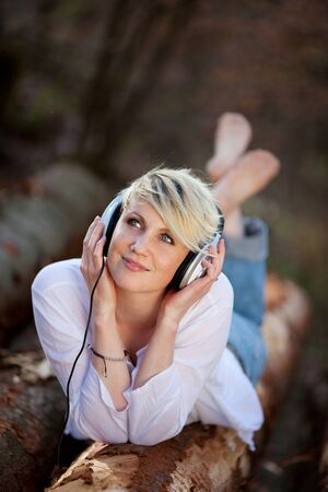 recorded: Portrait of a beautiful young woman with headphones lying on log Stock Photo