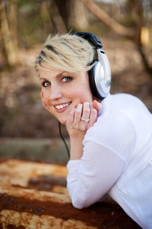immersed: Rear view of a young smiling woman with headphones lying on log outdoor