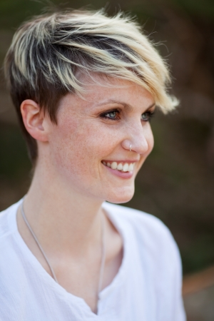 Closeup side view of a young happy blond woman with nose piercing Stock Photo