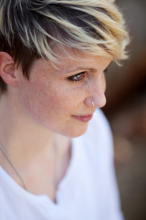 Closeup side view of a young blond woman with nose piercing photo