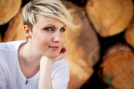 country side: Closeup portrait of thoughtful blond young woman looking away against stack of logs Stock Photo