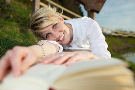Smiling young beautiful woman relaxing with a book by the country lake photo