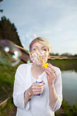 Happy young blond woman making soap bubbles by the country lake photo