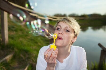 Closeup of a young blond woman making soap bubbles by the country lake Stock Photo - 21290190