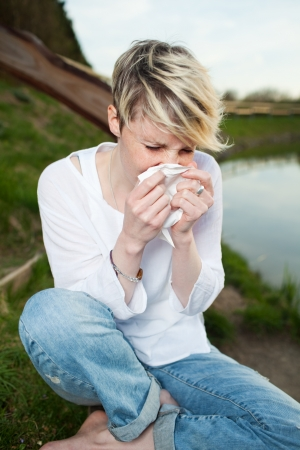 with pollen: Young woman sneezing into handkerchief by the lake