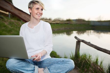 Portrait of a smiling young woman using laptop outdoors while looking away photo