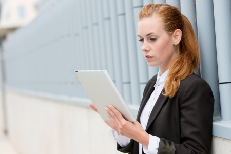 Young serious businesswoman reading ipad tablet against the wall photo