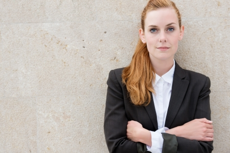 Portrait of a confident young businesswoman with arms crossed against the wall photo