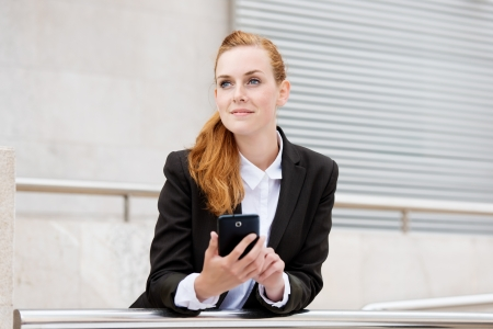 formals: Smiling attractive young businesswoman with a smartphone looking away Stock Photo