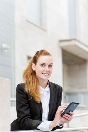 Happy attractive young redhead businesswoman with a smartphone looking away photo