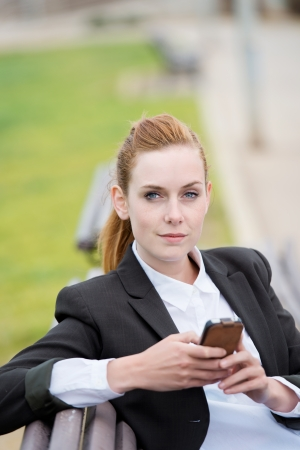 Portrait of a confident young businesswoman with mobile phone sitting in city park bench photo