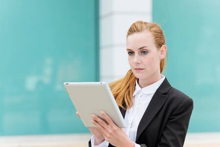 Smart young businesswoman using digital tablet outside photo