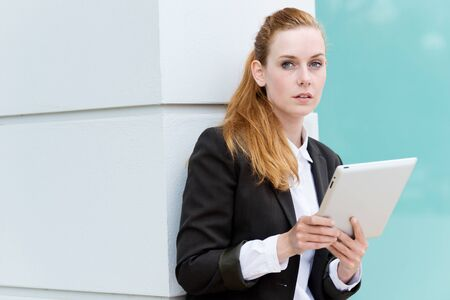 Serious redhead businesswoman with tablet PC looking in camera photo