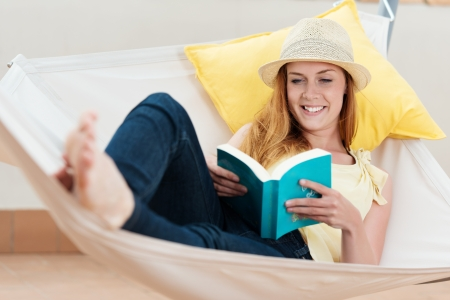 Smiling relaxed young woman reading book in the hammock Stock Photo - 21290307
