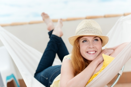 Happy and relaxed young woman daydreaming in hammock photo