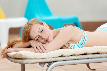 recliner: Side view of a smiling young redhead woman in deck chair Stock Photo