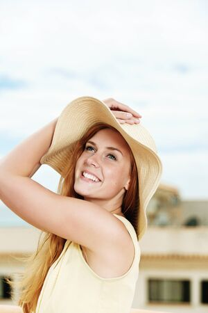 Cheerful young woman in strawhat standing the sky Stock Photo - 21290333
