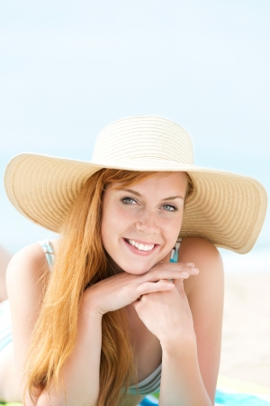 Portrait of a smiling young woman in sunhat lying at the beach Stock Photo - 21290339