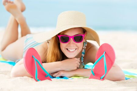 flipflops: Portrait of a smiling young woman in sunbathing at a beach