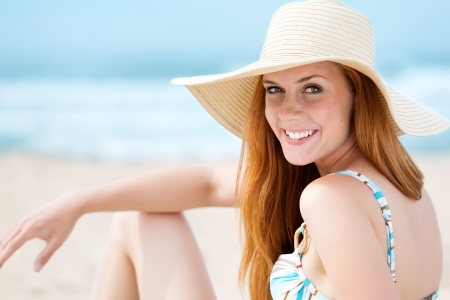 Portrait of a smiling young woman in sunhat at the beach photo