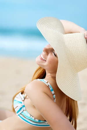 chillout: Beautiful smiling young woman in sunhat enjoying the sun at beach