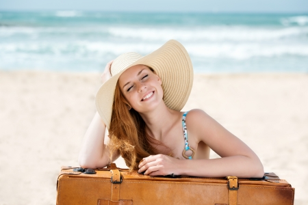 Beautiful smiling young woman in sunhat with suitcase at the beach photo